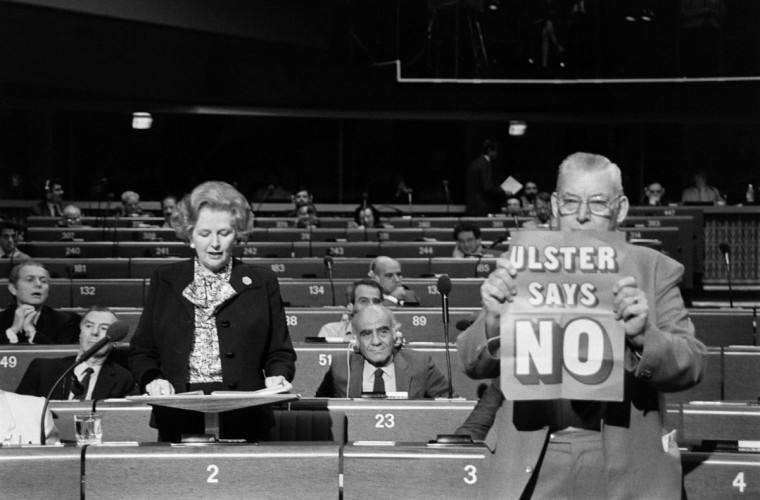 "In a file picture taken on 9 December, 1986, British Prime Minister Margaret Thatcher (L) delivers a speech at the European Parliament in Strasbourg as the leader of the Democratic Unionist Party Reverend Ian Paisley (R) brandishes a placard saying ""Ulster says no"". (Jean-Claude Delmas/AFP/Getty Images)"