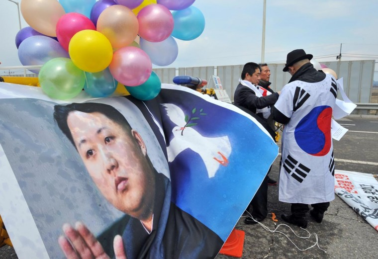 "South Korean activists set balloons on a banner showing pictures of North Korean leader Kim Jong-Un (L) and a dove of peace (C) during a rally urging regular operations of the Kaesong joint industrial complex on the road leading to North Korea at a military checkpoint in the border city of Paju on April 10, 2013. The banner reads ""We want National Defence Commission chairman Kim Jong-Un to put the Kaesong industrial complex back into operation immediately and stop nuclear and missile test launches for national peace"". South Korean and US forces raised their alert status to ""vital threat"" on April 10, ahead of an expected North Korean missile test, with tensions wound tight during a five-day buildup to a key anniversary. (Jung Yeon Jejung/AFP/Getty Images)"
