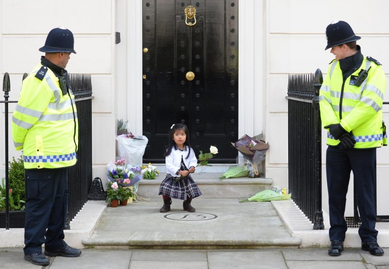 British police look on as a girl holds a rose amid floral tributes at the home of former British Prime Minister Margaret Thatcher in central London on April 10, 2013. British lawmakers will interrupt their holidays for a special session of parliament on April 10 to debate the legacy of Margaret Thatcher, who died on April 8 aged 87 after suffering a stroke. (Leon Neal/AFP/Getty Images)