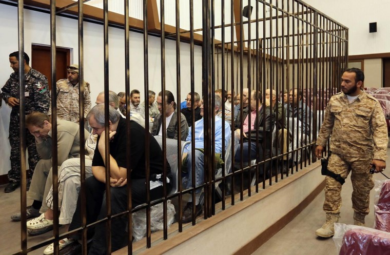 "Twenty-four Eastern Europeans citizens; 19 Ukrainians, three from Belarus and two Russians sit in a cell as they stand trial for serving as mercenaries for ousted Libyan slain leader Moamer Kadhafi during their hearing at the Military High Court in Tripoli on April 10, 2013. ""The trial was adjourned to May 1, 2013,"" said the president of the military court, acceding to the request of prosecutors and defense lawyers who have been committed by the Libyan government to defend the accused. (Mahmud Turkia/AFP/Getty Images)"