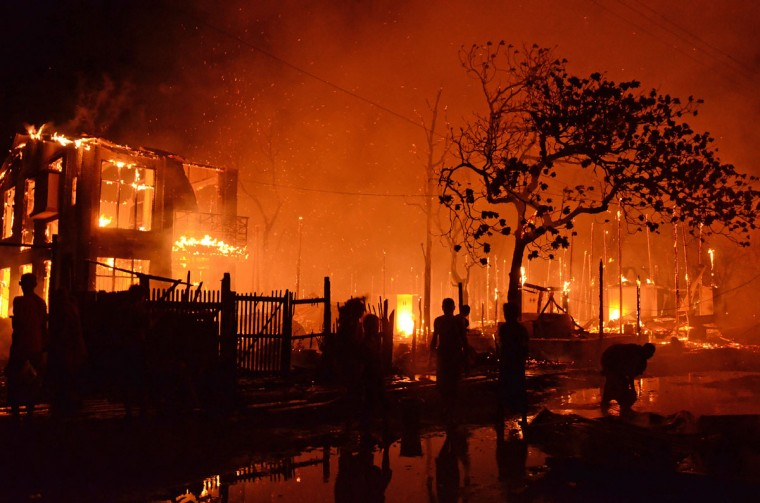 Residents stand by burning houses after a fire engulfed a township in Mandalay, central Myanmar. Some 200 houses were destroyed in the fire as the regional government was investigating the cause of the disaster. (Kyaw Zay WinK/AFP/Getty Images)