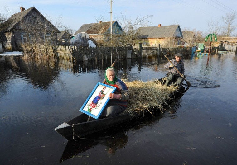 A man paddles on a boat with his wife in a flooded street during spring flood in a village of Vereshitsa near Pripyat river, some 300 km south of Minsk, Belarus. (Viktor Drachev/AFP/Getty Images)