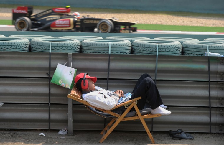 A track marshal sleeps as Lotus driver Kimi Raikkonen of Finland (background) drives past during the second practice session of the Formula One Chinese Grand Prix in Shanghai. (Peter Parks/AFP/Getty Images)