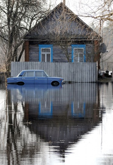 A car is parked near a house in a flooded street during spring flood in a village of Vereshitsa near Pripyat river, some 300 km south of Minsk. (Viktor Drachev/AFP/Getty Images)