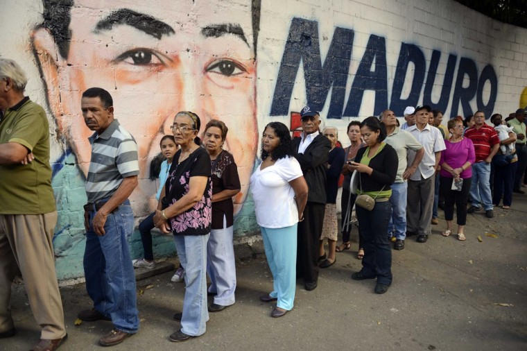 People line up to cast their vote at a polling station in Petare shantytown, Caracas, on April 14, 2013. Venezuelans headed to the polls on April 14 to elect Hugo Chavez's successor, with his political heir, Nicolas Maduro, hoping to continue his socialist revolution and rival Henrique Capriles vowing change in the divided nation. Leo Ramirez/AFP/Getty Images)