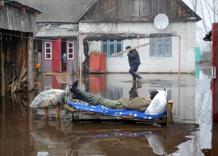 A man rests outdoor during spring flood in the Belarus village of Khvoensk, some 280 km south of Minsk, on April 14, 2013. (Viktor Drachev/AFP/Getty Images)