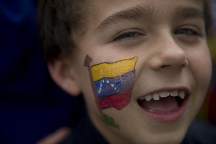 A Venezuelan boy living in Colombia accompanies her mother to vote in Bogota, on April 14, 2013. Venezuelans flocked to the polls Sunday to vote for Hugo Chavez's successor, choosing between the handpicked heir of his socialist revolution and an opponent vowing change in the divided nation. (Eitan Abramovich/AFP/Getty Images)