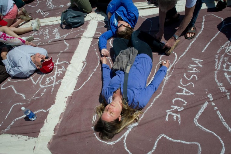 "Local artists trace an outline of their bodies with chalk to represent persons killed by guns, at the Lincoln Memorial reflecting pool as they take part in a ""flash mob"" performance in protest against gun violence in the US, April 14, 2013 in Washington DC. According to the organizers the ""art-meets-flash mob"" performance is a visual reflection of the destruction caused by gun violence. (Mladen Antonov/AFP/Getty Images)"