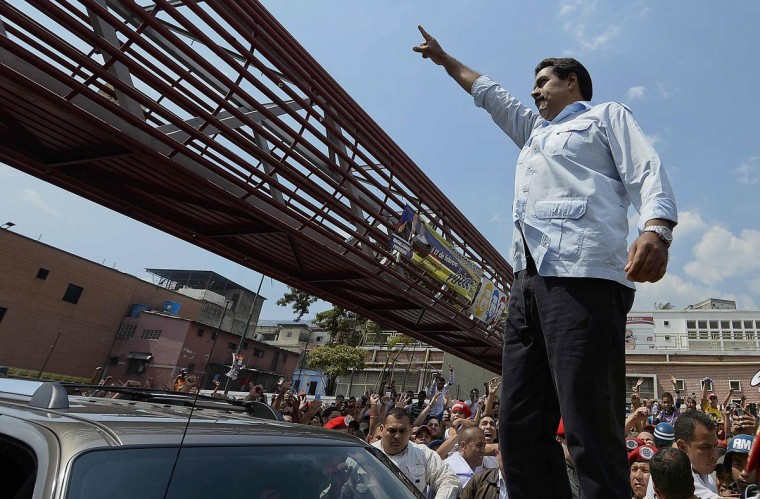 Venezuelan acting president and presidential candidate Nicolas Maduro gestures before casting his vote in Caracas, on April 14, 2013. Venezuelans flocked to the polls Sunday to vote for Hugo Chavez's successor, choosing between the handpicked heir of his socialist revolution and an opponent vowing change in the divided nation. (Juan Barreto/AFP/Getty Images)