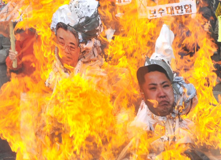 "Dozens of South Korean activists burn effigies with the portraits of North Korea's late president Kim Il-Sung (L) and his grandson and current leader Kim Jong-Un (R) as they shout ""Let's overthrow (Kim Jong-Un)!"" during an anti-Pyongyang rally in Seoul on April 15, 2013, to mark the late leader's 101st birthday. (Kim Jae-Hwan/AFP/Getty Images)"