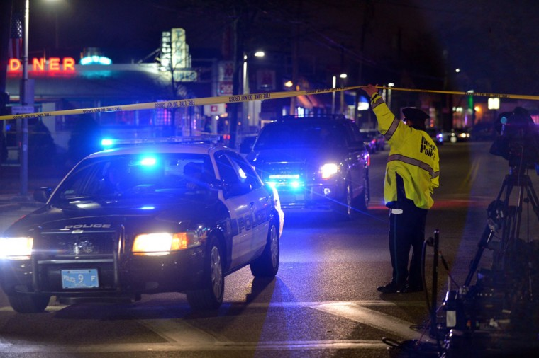 A Boston police officer allows police vehicles out of a closed area as a search for the second of two suspects wanted in the Boston Marathon bombings takes place April 19, 2013 in Watertown, Massachusetts. Police killed one of the suspected Boston marathon bombing suspects in a shootout early today and pursued a chaotic deadly street-to-street manhunt for his accomplice, officials said. (Stan Honda/AFP/Getty Images)