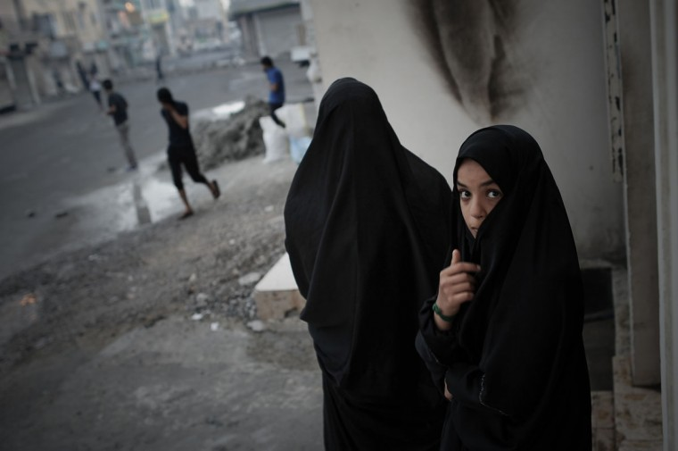 A Bahraini young girl poses during clashes between protesters and riot police following a protest against the arrival of Bahrain Formula One Grand Prix on April 18, 2013 in the village of Diraz, west of Manama. Bahrain riot police fired tear gas and stun grenades at protesters who hurled petrol bombs during protests against the staging of the race. (Mohammed Al-Shaikh/AFP/Getty Images)
