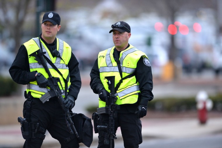 Two police officers stand guard at the perimeter of a locked down area as a search for the second of two suspects wanted in the Boston Marathon bombings takes place April 19, 2013 in Watertown, Massachusetts. Police killed one of the suspected Boston marathon bombing suspects in a shootout early today and pursued a chaotic deadly street-to-street manhunt for his accomplice, officials said. (Stan Honda/AFP/Getty Images)