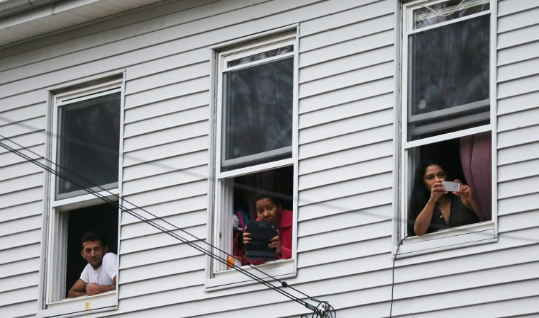 Onlookers take pictures as they watch from windows while SWAT team members search for one remaining suspect at a neighboring apartment building in Watertown, Massachusetts. Earlier, a Massachusetts Institute of Technology campus police officer was shot and killed at the school's campus in Cambridge. (Mario Tama/AFP/Getty Images)