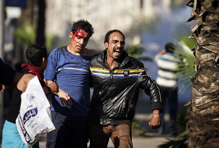 A man shouts as he helps an injured man during clashes between Muslim Brotherhood members and opponents in central Cairo. Egyptian Islamist protesters clashed with opponents in central Cairo, with both sides pelting each other with stones as the sounds of shots were heard, an AFP journalist said. (Gianluigi Guercia/AFP/Getty Images)