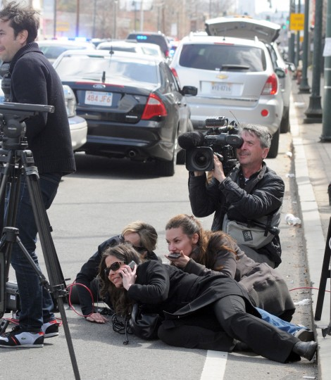 Journalists take cover during the manhunt for the second suspect of the Boston Marathon bombing in Watertown, Massachusetts, on April 19, 2013. The first suspect was killed during a police gunfight earlier in the day. Thousands of heavily armed police staged an intense manhunt Friday for a Chechen teenager suspected in the Boston marathon bombings with his brother, who was killed in a shootout. Dzhokhar Tsarnaev, 19, defied the massive force after his 26-year-old brother Tamerlan was shot and suffered critical injuries from explosives believed to have been strapped to his body. (John Mottern/AFP/Getty Images)