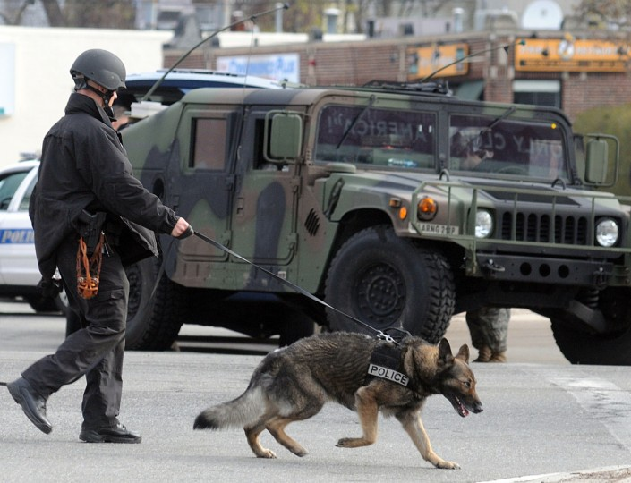 A K-9 unit takes part in the Watertown, Massachusetts manhunt for the second suspect in the Boston Marathon bombing who is still at large on April 19, 2013. Thousands of heavily armed police staged an intense manhunt Friday for a Chechen teenager suspected in the Boston marathon bombings with his brother, who was killed in a shootout. Dzhokhar Tsarnaev, 19, defied the massive force after his 26-year-old brother Tamerlan was shot and suffered critical injuries from explosives believed to have been strapped to his body. (John Mottern/AFP/Getty Images)