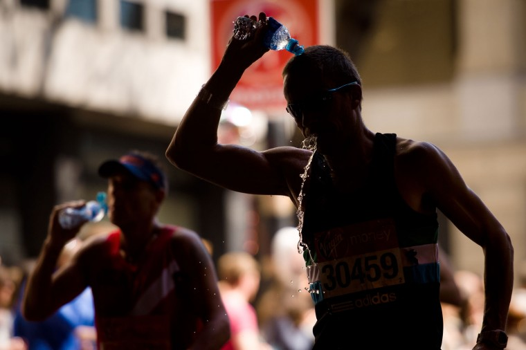A runner pours water on his head to cool off. (Getty Images)