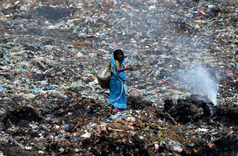An Indian ragpicker walks among heaps of rubbish at a municipal waste dump in Dimapur on World Earth Day. (STRDEL/AFP/Getty Images)