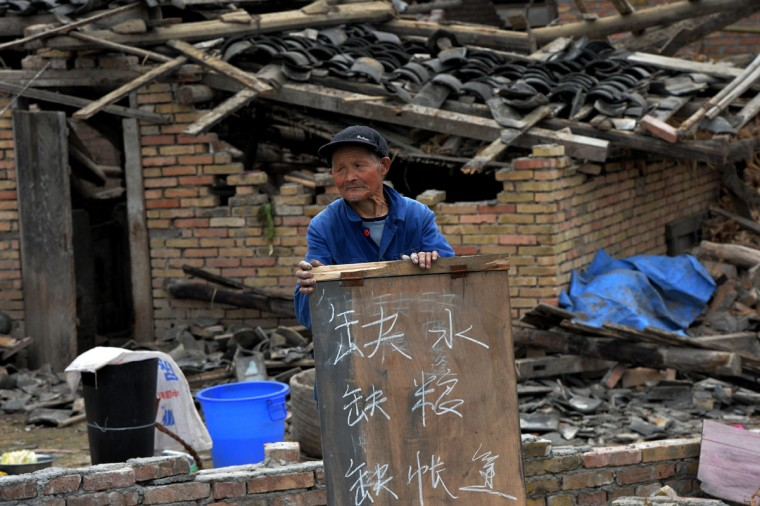 An elderly man holds a sign asking for help outside his destroyed home in Longmen village after a magnitude 7.0 earthquake hit Lushan, Sichuan Province, (Mark Ralston/AFP/Getty Images)