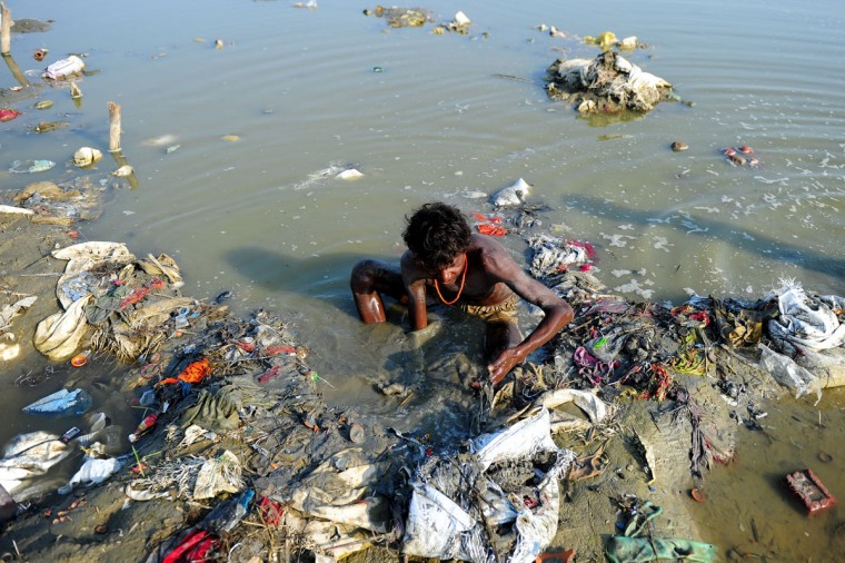 An Indian youth searches through mud for coins and other items of value in the polluted banks of the River Ganges at Sangam in Allahabad during World Earth Day. (Sanjay Kanojia/AFP/Getty Images)
