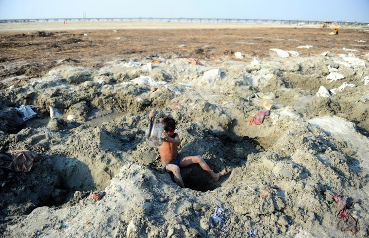 An Indian youth digs digs a hole through caked up mud, in search for coins and other items of value, from the polluted banks of the River Ganges at Sangam in Allahabad during World Earth Day. (Sanjay Kanojia/AFP/Getty Images)