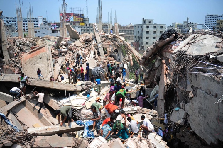 Bangladeshi civiliant volunteers assist in rescue operations after an eight-storey building collapsed in Savar, on the outskirts of Dhaka, on April 24, 2013. At least 82 people were killed and many more feared dead when an eight-storey building housing a market and garment factory collapsed in Bangladesh on Wednesday, officials said. (Munir uz Zaman/AFP/Getty Images)