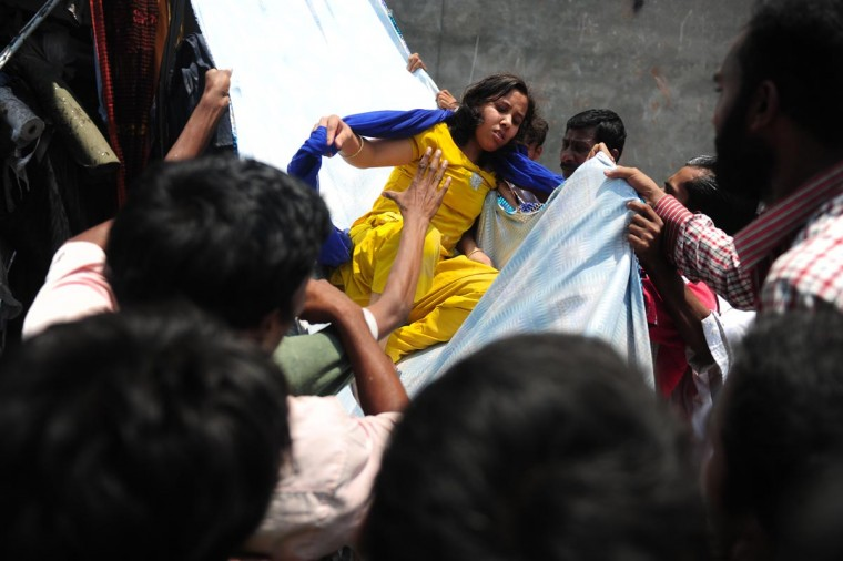 Bangladeshi garment workers assist a survivor after sliding down a length of textile after an eight-storey building collapsed in Savar, on the outskirts of Dhaka, on April 24, 2013. At least 82 people were killed and many more feared dead when an eight-storey building housing a market and garment factory collapsed in Bangladesh on Wednesday, an official said. (Munir uz Zaman/AFP/Getty Images)