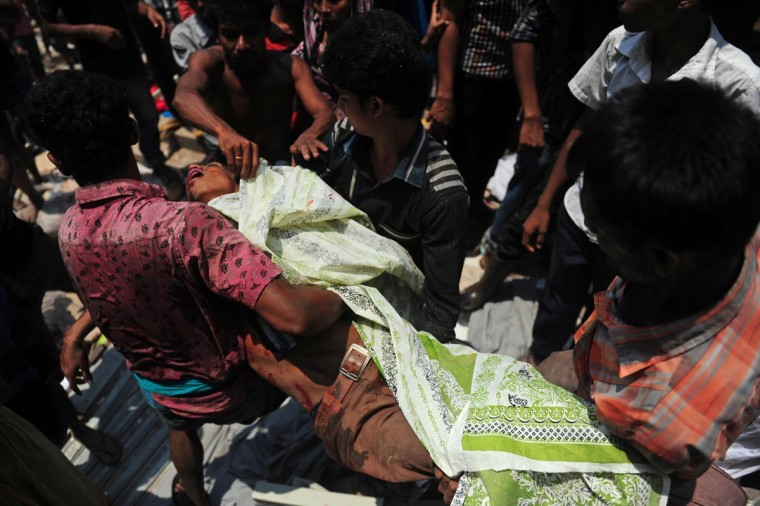 Bangladeshi garment workers carry a victim's body after an eight-storey building collapsed in Savar, on the outskirts of Dhaka, on April 24, 2013. At least 82 people were killed and many more feared dead when an eight-storey building housing a market and garment factory collapsed in Bangladesh on Wednesday, an official said. (Munir uz Zaman/AFP/Getty Images)