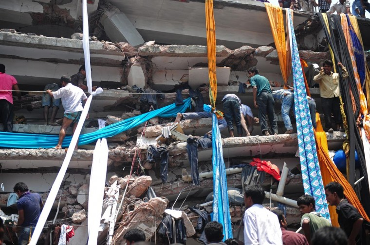 Bangladeshi volunteers prepare lengths of textiles to used as evacutation slides for the injured and dead after an eight-storey building collapsed in Savar, on the outskirts of Dhaka, on April 24, 2013. At least 82 people were killed and many more feared dead when an eight-storey building housing a market and garment factory collapsed in Bangladesh on Wednesday, an official said. (Munir uz Zaman/AFP/Getty Images)