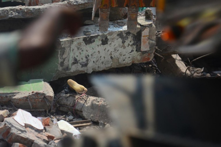 The foot of a victim is seen amid the rubble after an eight-storey building collapsed in Savar, on the outskirts of Dhaka, on April 24, 2013. At least 60 people were killed and many more feared dead when an eight-storey building housing a market and garment factory collapsed in Bangladesh on Wednesday, an official said. (Munir uz Zaman/AFP/Getty Images)