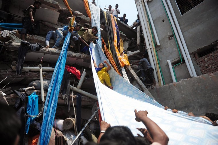 TOPSHOTS Bangladeshi garment workers help evacuate a survivor using lengths of textile as a slide to evacuate from the rubble after an eight-storey building collapsed in Savar, on the outskirts of Dhaka, on April 24, 2013. At least 82 people were killed and many more feared dead when an eight-storey building housing a market and garment factory collapsed in Bangladesh on Wednesday, officials said. (Munir uz Zaman/AFP/Getty Images)