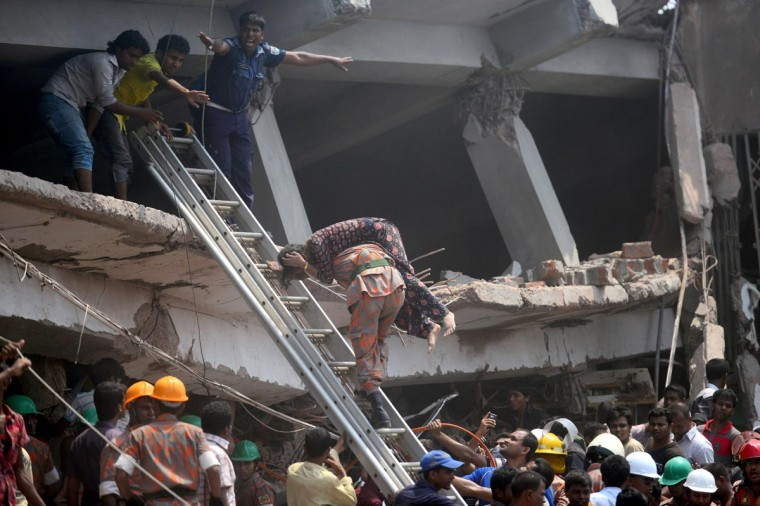 TOPSHOTS A Bangladeshi firefighter carries an injured garment worker after an eight-storey building collapsed in Savar, on the outskirts of Dhaka, on April 24, 2013. At least 82 people have died and 700 are injured after a eight-storey building housing several garment factories collapsed on the outskirts of Bangladesh's capital on Wednesday, a doctor said. (Munir uz Zaman/AFP/Getty Images)