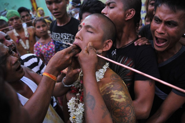 A Hindu devotee (C) has his body pierced during a Hindu festival in Yangon on 25th April 2013. Although only an estimated two per cent of Myanmar's population practice Hinduism in this majority Buddhist country, most of them being Myanmar Indians, Hindu influences can be found in the Myanmar language, culture and the architecture of cities such as Bagan. (Ye Aung Thu/AFP/Getty Images)