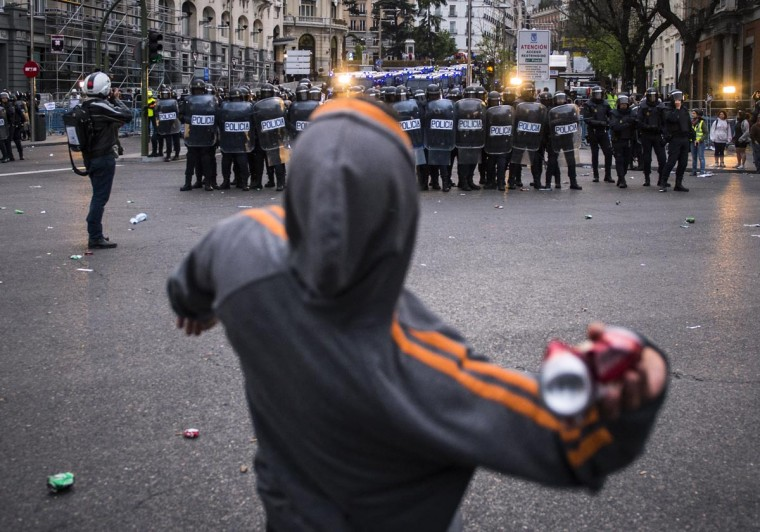 """A man throws a can at anti-riot policemen clashing with demonstrators trying to besiege the Spain's parliament (Las Cortes) during an anti-government demonstration in Madrid on April 25, 2013. A thousand of people, mostly youths, gathered today evening near the Spanish parliament in Madrid in response to a call by a hardline protest movement for demonstrators to """"Besiege Congress"""" indefinitely to force the government to quit. (Dani Pozo/AFP/Getty Images)"""