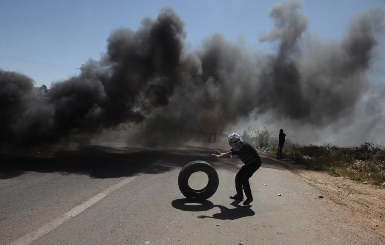 A Palestinian demonstrator from the West Bank village of Deir Jarir, northeast of Ramallah, rolls a tire near rising smoke during clashes with Israeli soldiers following a march against construction on their land by members of the Jewish settlement of Ofra on April 26, 2013. (Abbas Momani/AFP/Getty Images)
