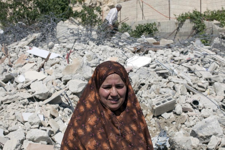 A female member of the Palestinian Ghaith family stands with the rubble of her home to her back after it was demolished by Jerusalem municipality workers in al-Tur on April 29, 2013. Palestinian homes built without an Israeli construction permit are often demolished by order of the Jerusalem municipality. (Ahmad Gharabali/AFP/Getty Images)