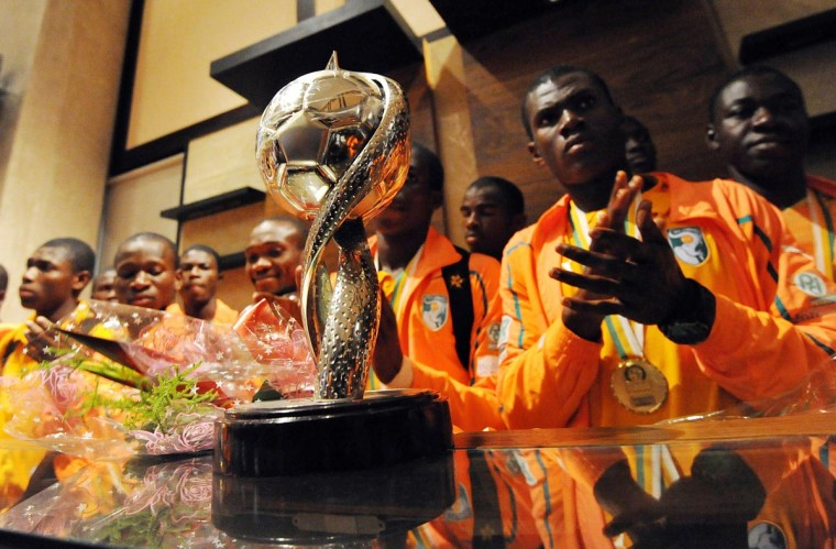 "Ivory Coast's junior football national team players dubbed, ""Elephanteaux"" (Baby Elephants), pose in front of the 2013 CAN U17 tournament winners trophy upon their arrival at Abidjan's airport on April 29, 2013. Their arrival comes two days after the Elephanteaux won, for the first time, the CAN U17 in Morocco. Ivory Coast defeated Nigeria 5-4 in a penalty shoot out. (Sia Kambou/AFP/Getty Images)"