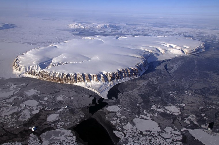 This April 20, 2013 NASA handout image shows Saunders Island and Wolstenholme Fjord with Kap Atholl in the background seen during an IceBridge survey flight near Qaasuitsup, Greenland. Sea ice coverage in the Fjord ranges from thicker, white ice seen in the background, to thinner grease ice and leads showing open ocean water in the foreground. (NASA HO via Michael Studinger/AFP/Getty Images)