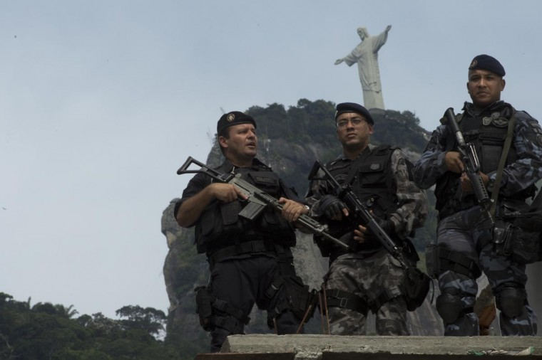 Backdropped by the Corcovado Hill, members of Rio de Janeiro's feared military police battalion BOPE stand guard at Guararapes shantytown on April 29, 2013 before the specially-trained police force known as Police Pacification Units or UPP, can be deployed in. The operation is part of a government strategy designed to combat crime and reassert full control of the Rio de Janeiro metropolis ahead of the upcoming FIFA Confederations Cup, the football World Cup of 2014 and the Olympic Games two years later. (Christophe Simon/AFP/Getty Images)