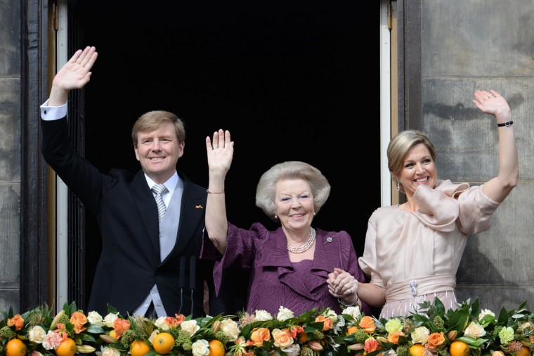 King Willem-Alexander of the Netherlands (left), his mother Princess Beatrix and his wife Queen Maxima wave to the crowd of Dam Square from the balcony of the Royal Palace in Amsterdam. (Patrick Stollarz/AFP/Getty Images)