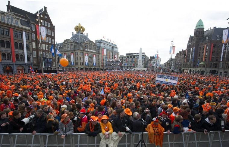 Members of the public gather in Dam Square in front of the Royal Palace in central Amsterdam as they wait for members of the royal family to appear as Queen Beatrix abdicates and hands the throne to her son Willem-Alexander. (Carl Court/AFP/Getty Images)