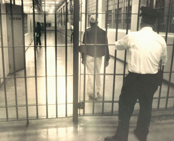 A corrections officer at the city jail locks a barred gate behind a detainee as he moves from one section of the crowded jail to another in 1976. (Irving H. Phillips/ Baltimore Sun)