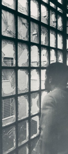 A city jail detainee looks out through locked windows smashed during a riot in 1971. (George Cook/Baltimore Sun)