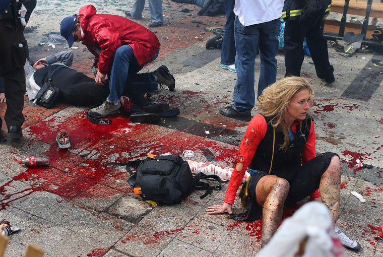 Nicole Gross (right) of Charlotte, NC, sits injured at the scene of the first explosion that went off near the finish line of the Boston Marathon. (John Tlumacki/The Boston Globe via Getty Images)