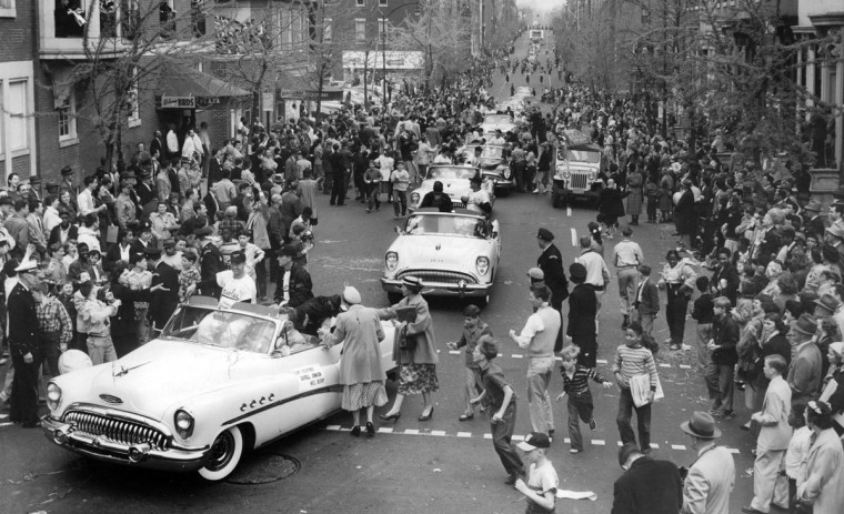 Mobs of people crowd the ball players on Charles and Madison Street at the 1954 Orioles Opening Day. (Clarence B. Garrett./Baltimore Sun)