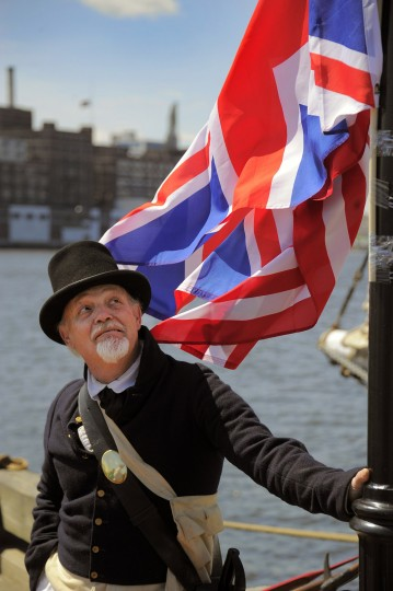 Dave Gorrell represents the Fort McHenry Guard as the 1812 flag and the British ensign flag flutter above him. (Karl Merton Ferron/Baltimore Sun photo)