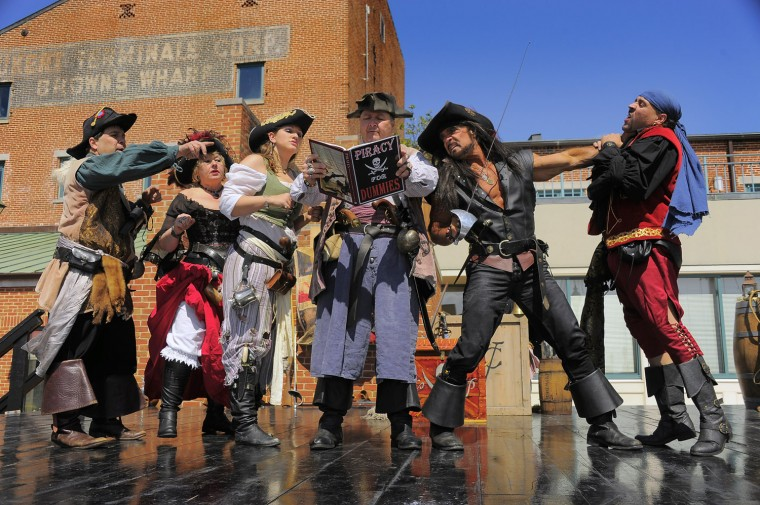 "Members of Valhalla's Pirates listen to Matthew Mayhem read from a book labeled ""Piracy for Dummies."" (Karl Merton Ferron/Baltimore Sun photo)"