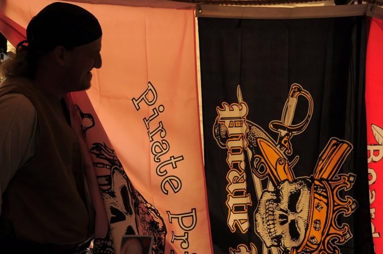 "Raymond Leibach, aka ""Cashmere Cel Vidra"" of Allentown, Pa. is silhouetted against pirate flags. (Karl Merton Ferron/Baltimore Sun photo)"