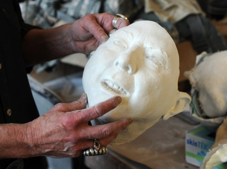 Artist Lania D'Agostino of D'Agostino Studios holds a resin head. This is the final product in a mult-step casting process that begins with the actual head of a person. (Algerina Perna/Baltimore Sun)